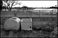 Discarded tank, bath and trolley B&W